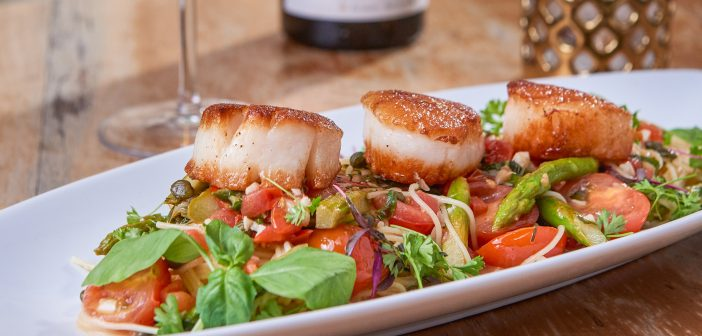 Enjoy delicious dishes at Nick & G's such as their Seared Maine Diver Scallops & Asparagus.